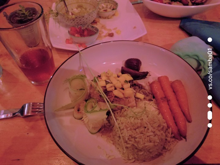 A plate of locally sourced food including rice, fish, carrots, pineapple, and cucumber. A dish for the article Eating in Jaco, Costa Rica.