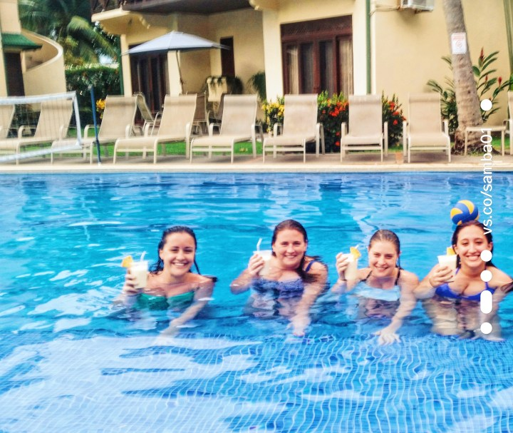 Four girls raise their glasses while sitting in a pool in Jaco, Costa Rica