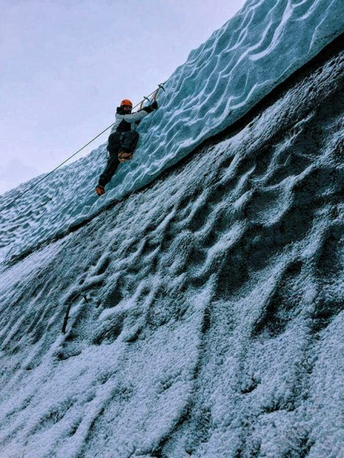 A man scales a wall made of ice in Solheimajokull in Iceland