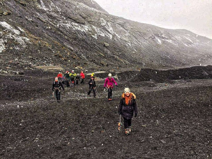 A group of people walk across a valley of ash to get to Solheimajokull glacier