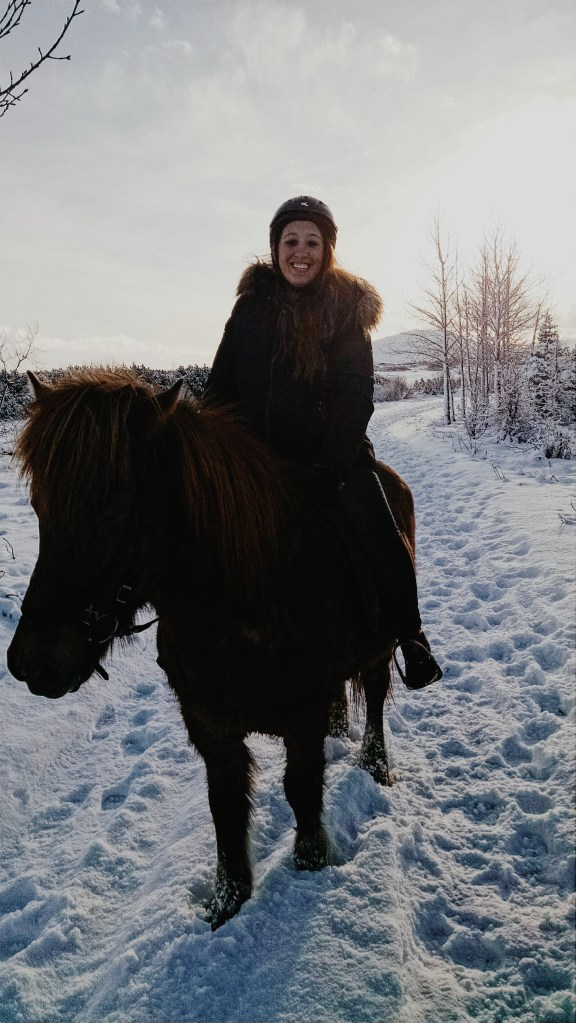A woman rides an Icelandic horse through the snow in Iceland