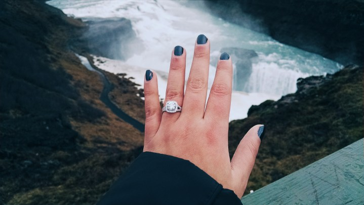 A woman showing her hand with new engagement ring over Gullfoss Falls