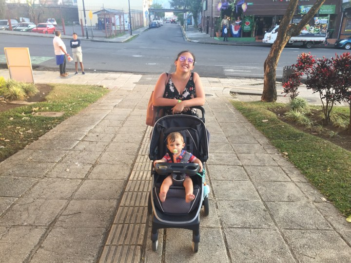A mother in sunglasses wheels her baby around in a stroller through the streets of San Jose, Costa Rica.