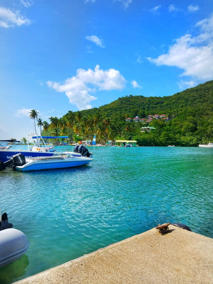 A view of Marigot Bay with beautiful blue waters, some boats, and lush green mountains and palm trees. This certainly got me in the mood for my trip to St Lucia with a friend!