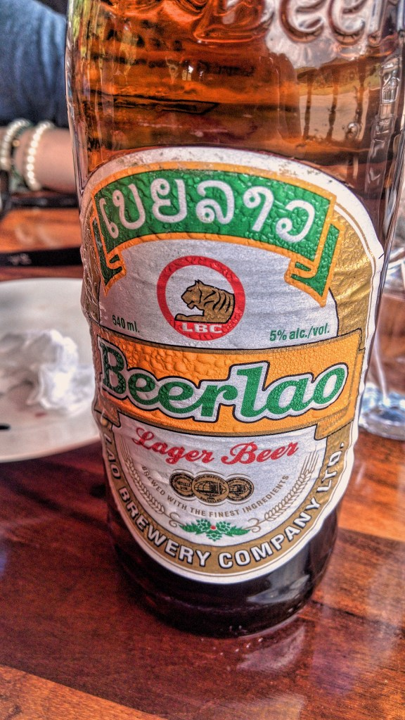 "A bottle of ""Beerlao"" with its yellow, gold, green, and white label and tiger emblem"