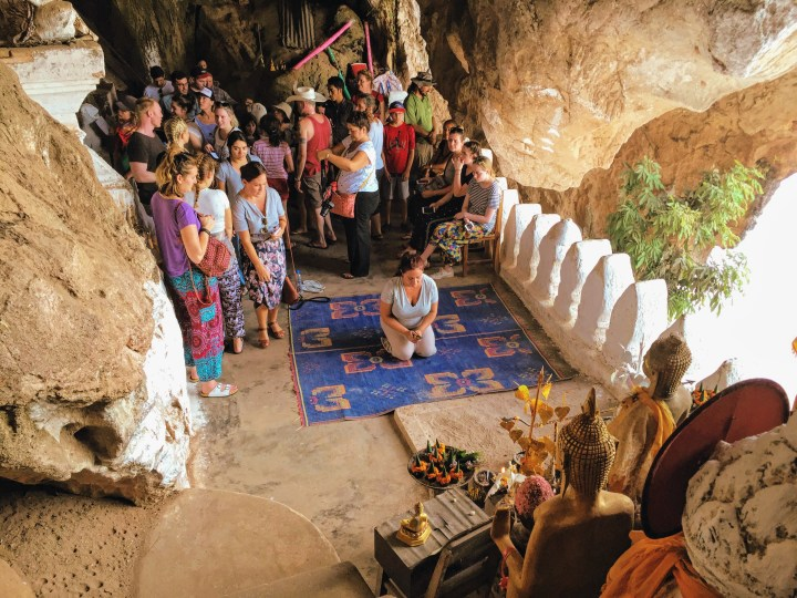 A woman kneels on a prayer mat in the Pak Ou caves. She is shaking a cup full of numbered sticks with an altar in front of her. A group of people wait behind her and look on.