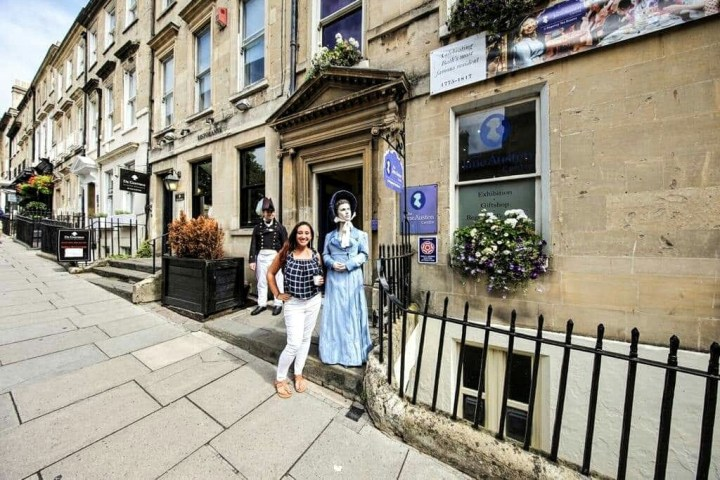 A woman in white pants and a blue checkered tank top stands next to a statue of Jane Austen while visiting the Jane Austen Centre in Bath, England