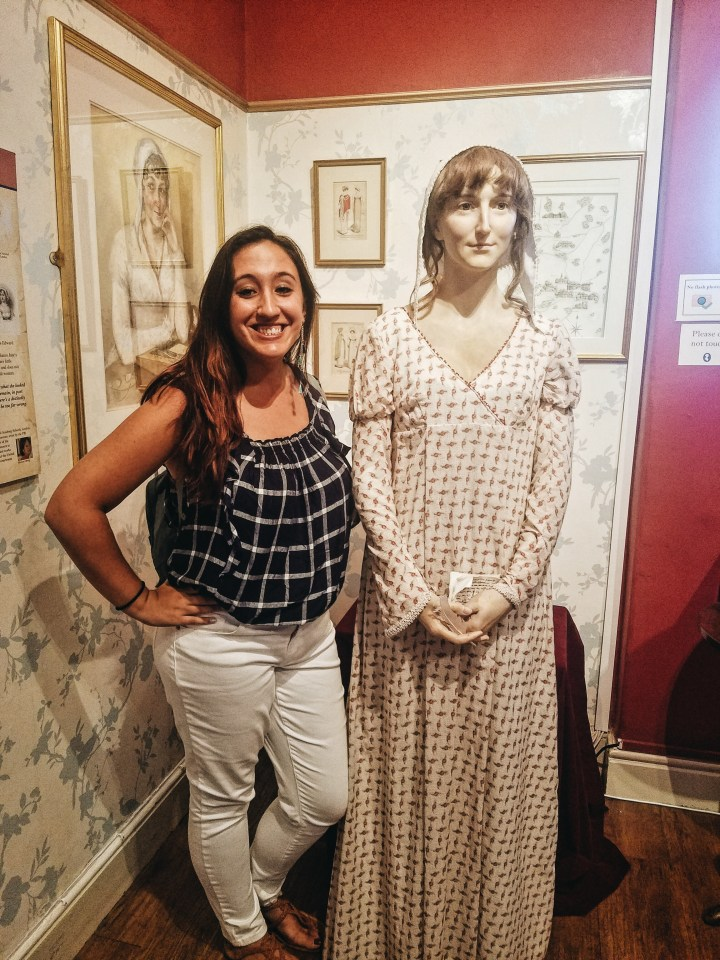 A woman stands with a Jane Austen wax figure while visiting the Jane Austen Centre in Bath, England
