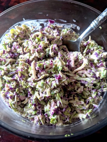 A bowl of the Whole30, paleo, keto, and vegan optional recipe for the Brussel sprout, broccoli, and red cabbage coleslaw