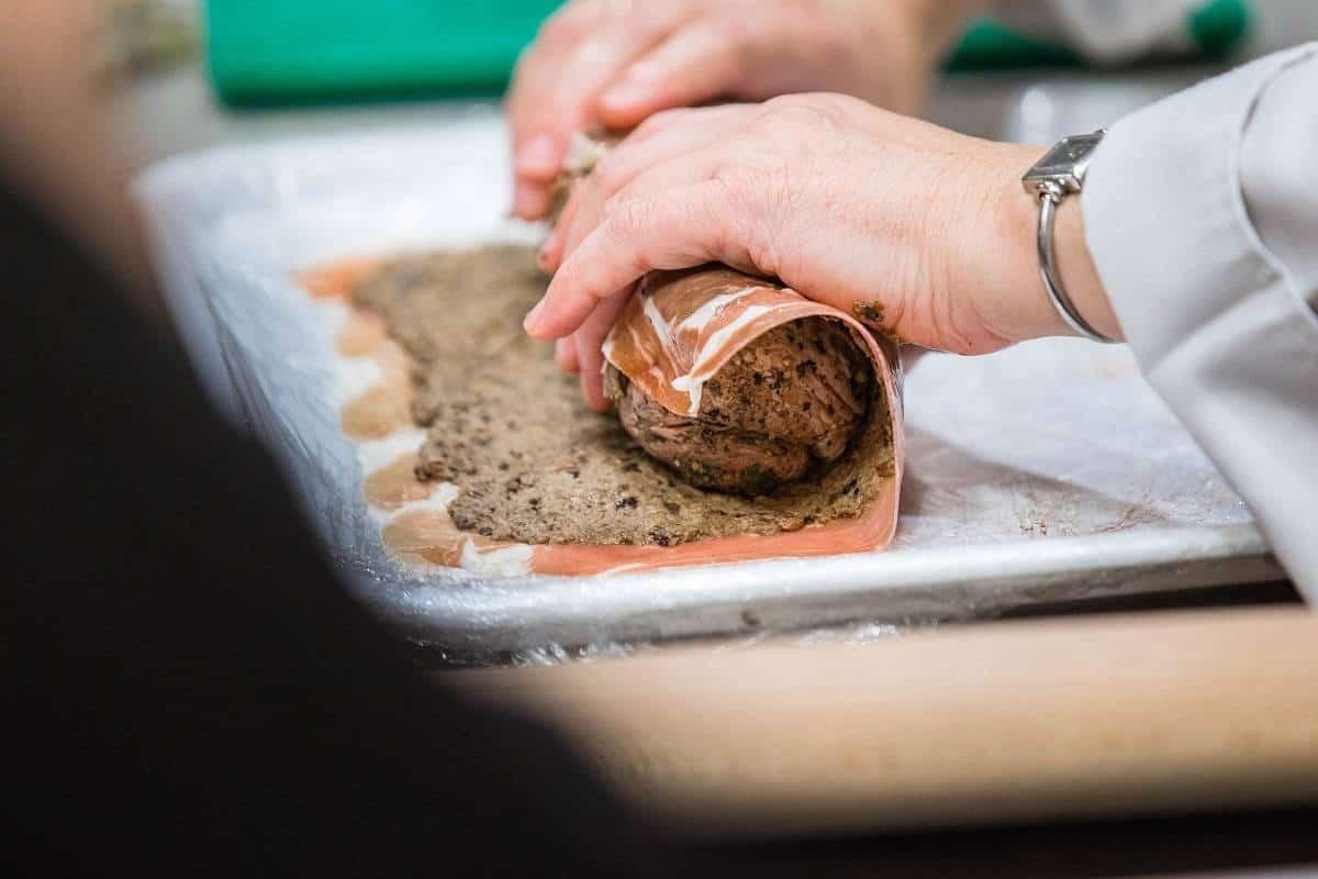 Rolling the pork tenderloin in the Parma Ham