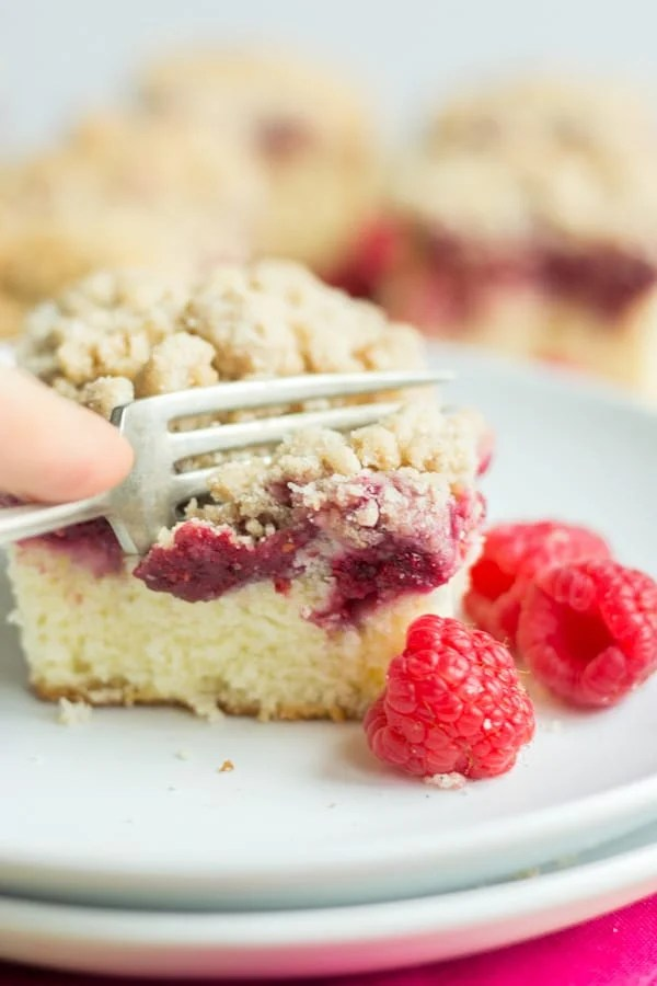 Raspberry Crumb Cake! Crumble fans rejoice because this moist and delicious cake is topped with a sweet and fruity raspberry jam (plus real raspberries) and piled high with cinnamon crumble. It's so easy to make and the perfect morning cake to go with your Valentine's Day brunch.
