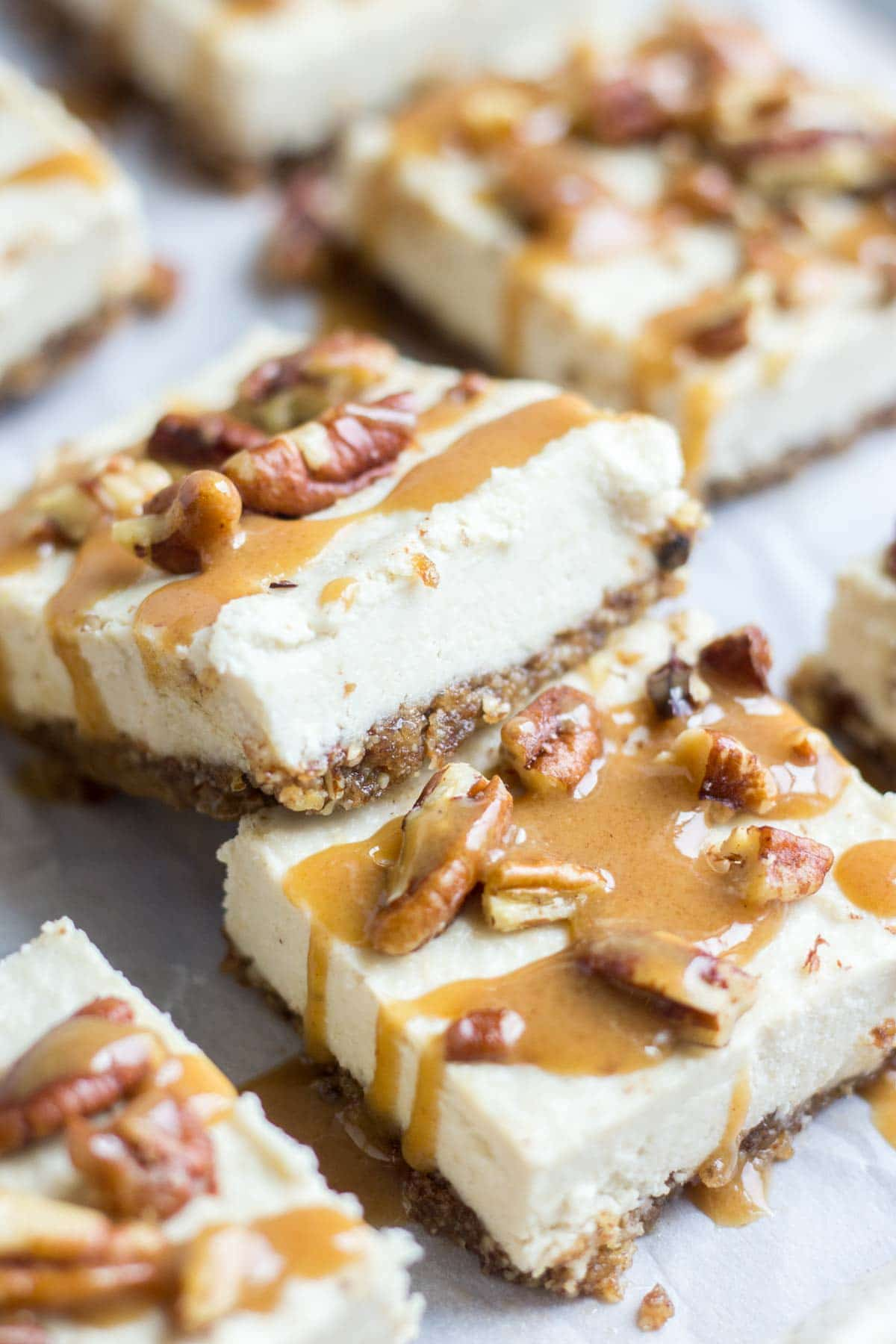 Smooth and creamy, these turtle vegan cheesecake bars are an easy and no bake healthy dessert. The crust is made with pecans and dates and the silky vegan cheesecake is topped with paleo caramel and pecans. You won't believe how yummy an easy it is to make!