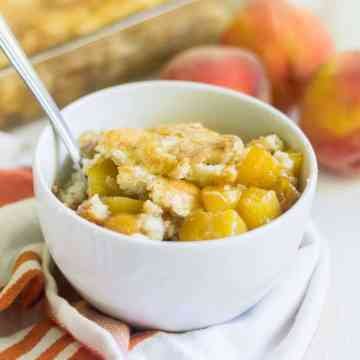 This Gluten Free Peach Cobbler is made with fresh peaches, cinnamon and a gluten free cobbler topping you will drool over. Your friends and family won't even know it's gluten free!
