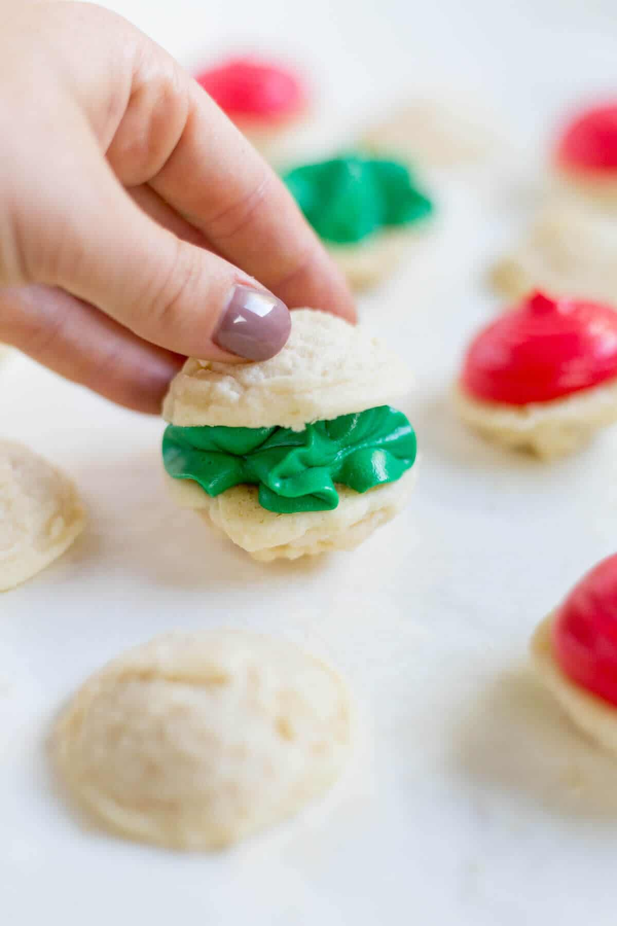 Melting moments sandwich cookies are a must-make Christmas cookie! They're tiny cookies sandwiched with a thick and creamy frosting dyed red and green. This festive cookie recipe will be a new family favorite.