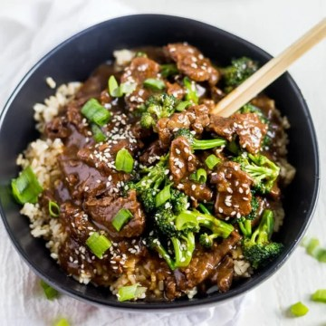 healthy mongolian beef over rice in a black bowl with chop sticks