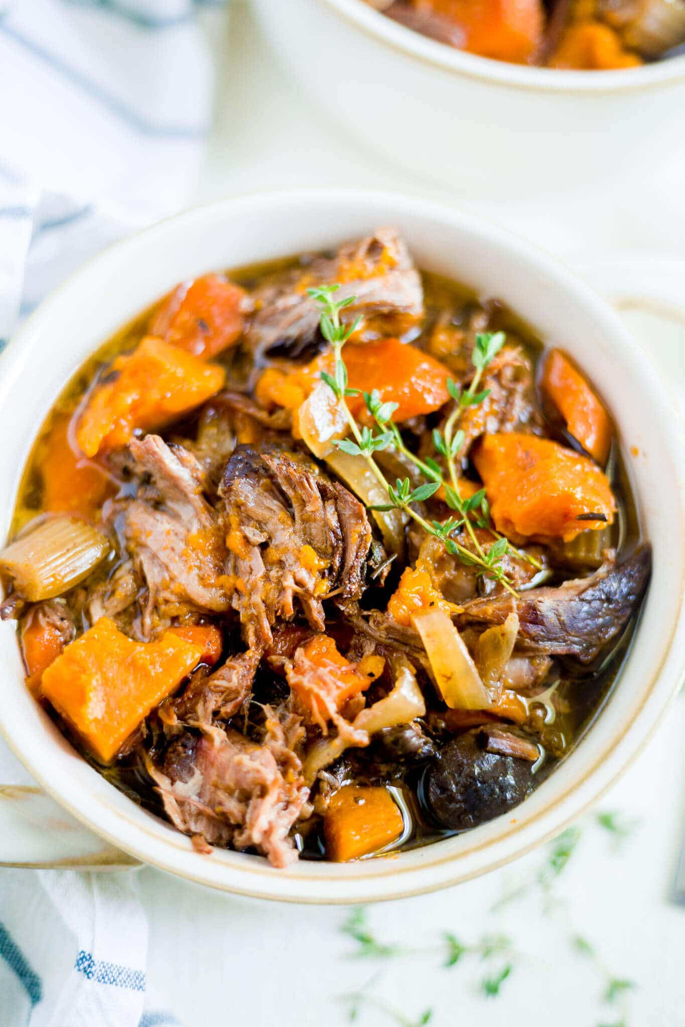 beef and sweet potato stew in a bowl with fresh thyme