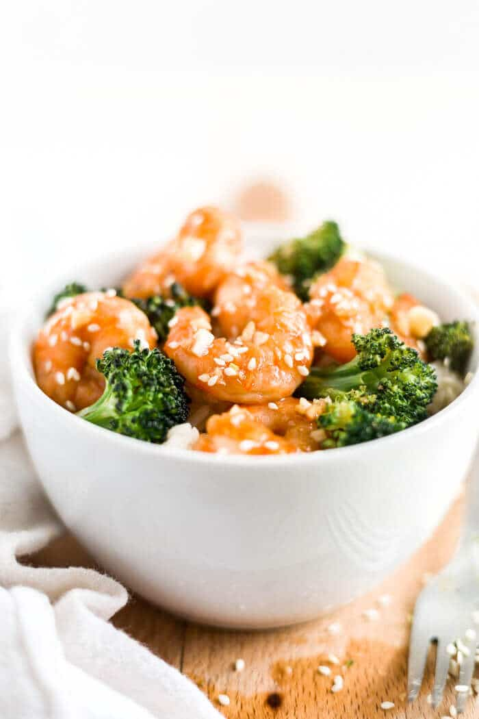 honey garlic shrimp in a bowl with rice and broccoli with a fork and sesame seeds