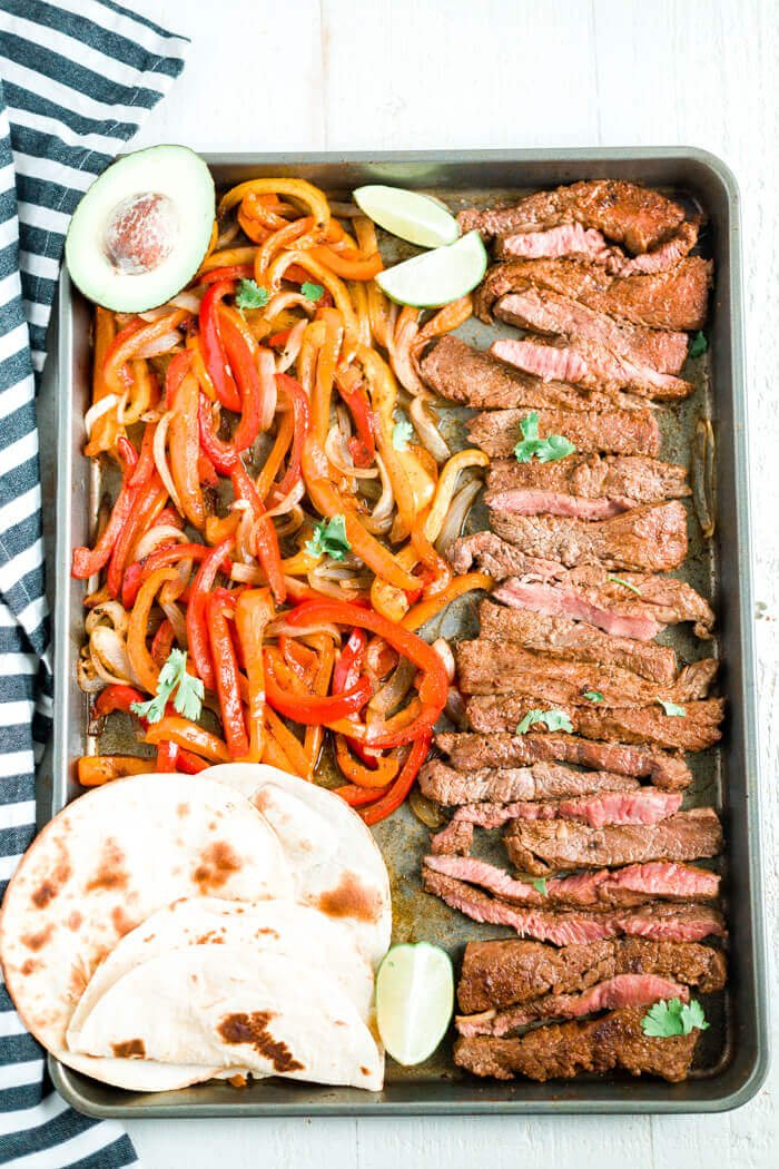 sheet pan steak fajitas on a tray with avocado, cilantro and toasted toritillas