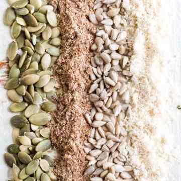 pumpkin seeds, ground flax seeds, sunflower seeds and ground sesame seeds on a table for seed cycling