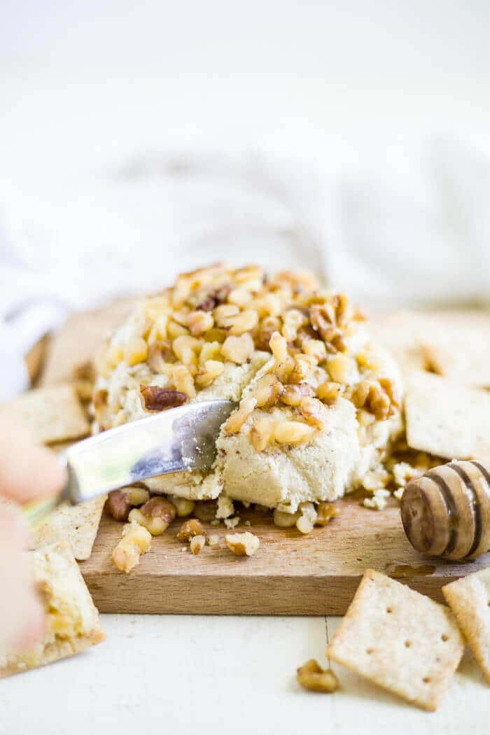 knife slicing honey walnut vegan cheese spread on a cutting board