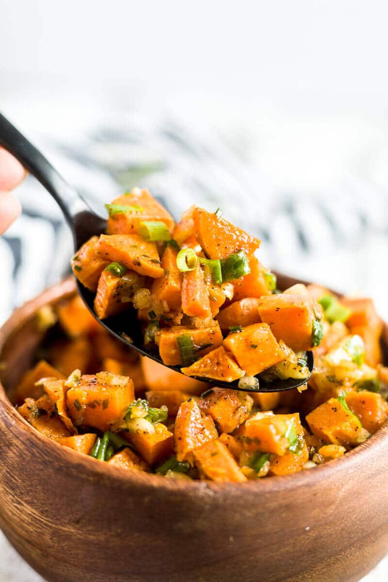 sweet potato salad recipe being scooped out of a wooden bowl