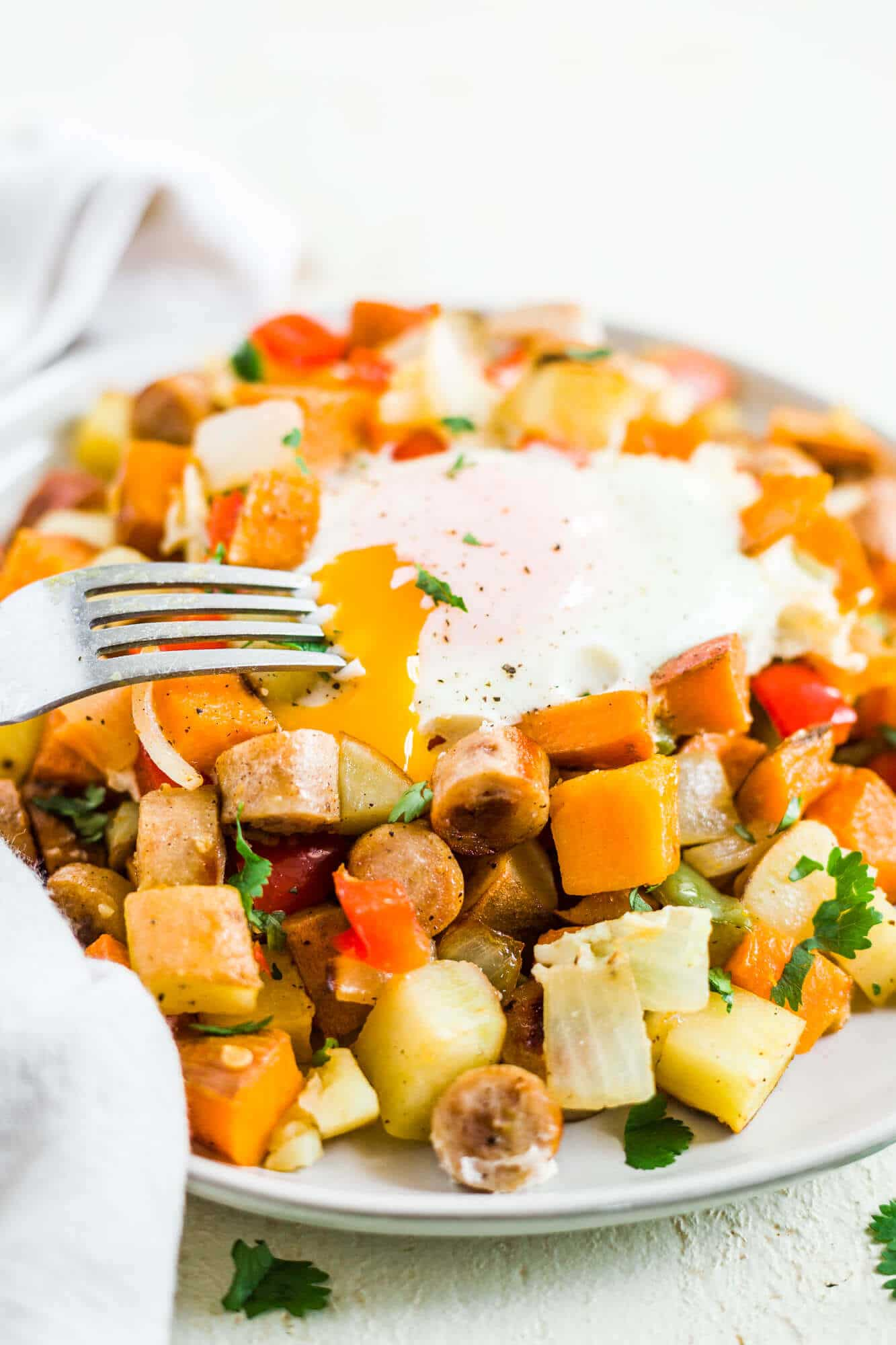 healthy sweet potato breakfast hash on a plate with an over easy egg