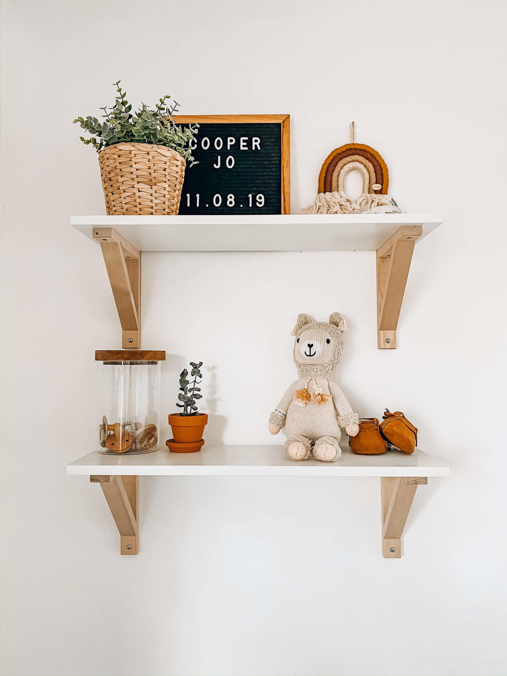 white and wood modern shelves for boho nursery from ikea with decor on top