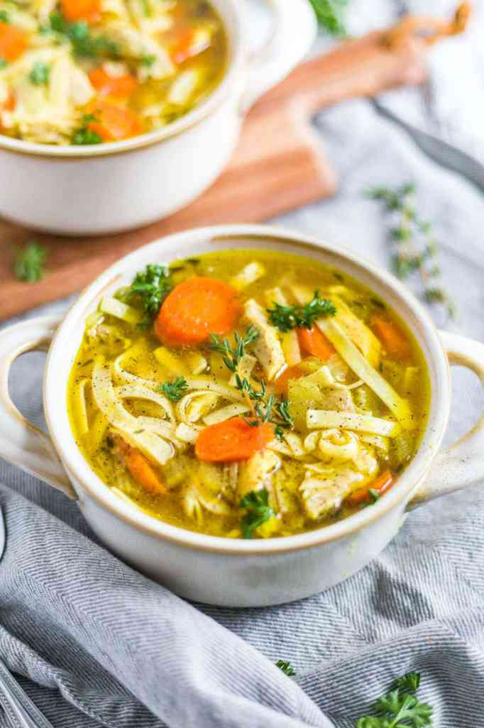 instant pot chicken noodle soup in a white bowl on a gray napkin