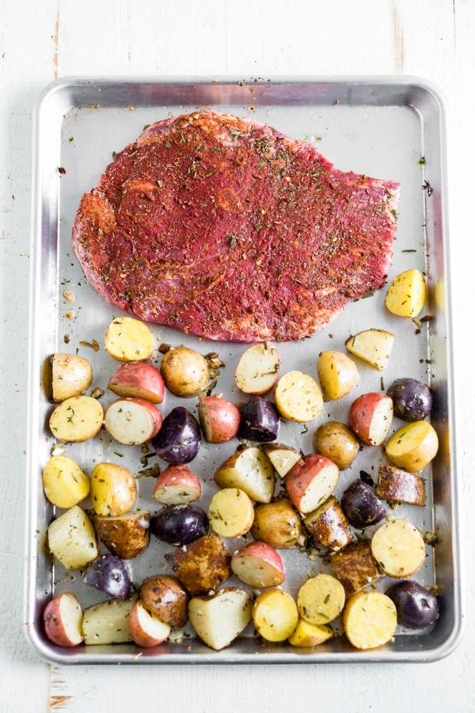 steak and potatoes on sheet pan before cooking in the oven