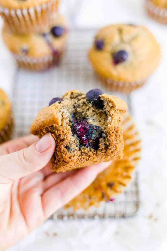 Hand holding a blueberry muffin with a bite taken out