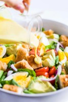 honey mustard dressing being poured on crispy chicken salad