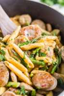 a wooden spoon scooping out chicken asparagus pasta