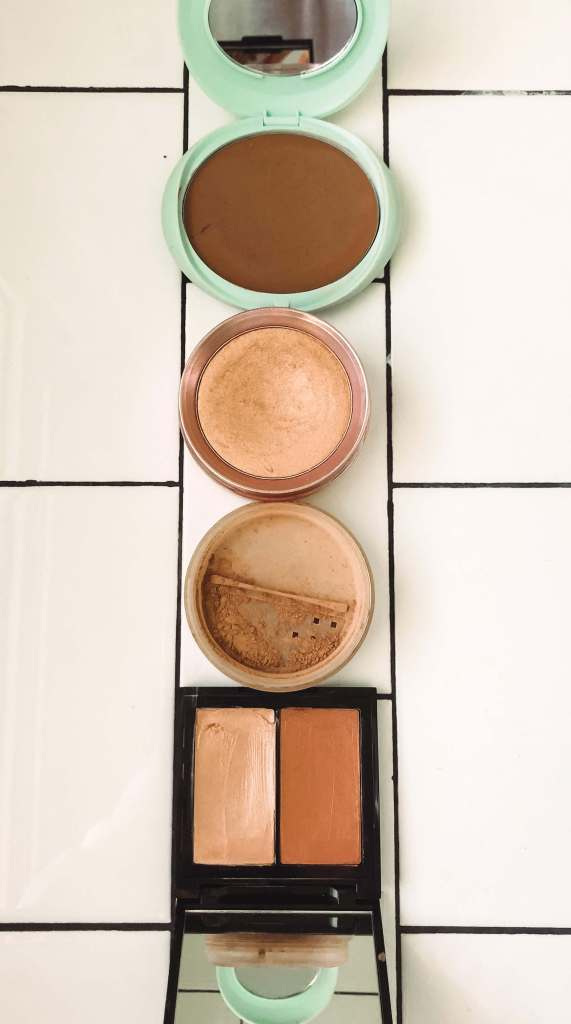 bronzer, blush and highlighter sitting on white subway tile