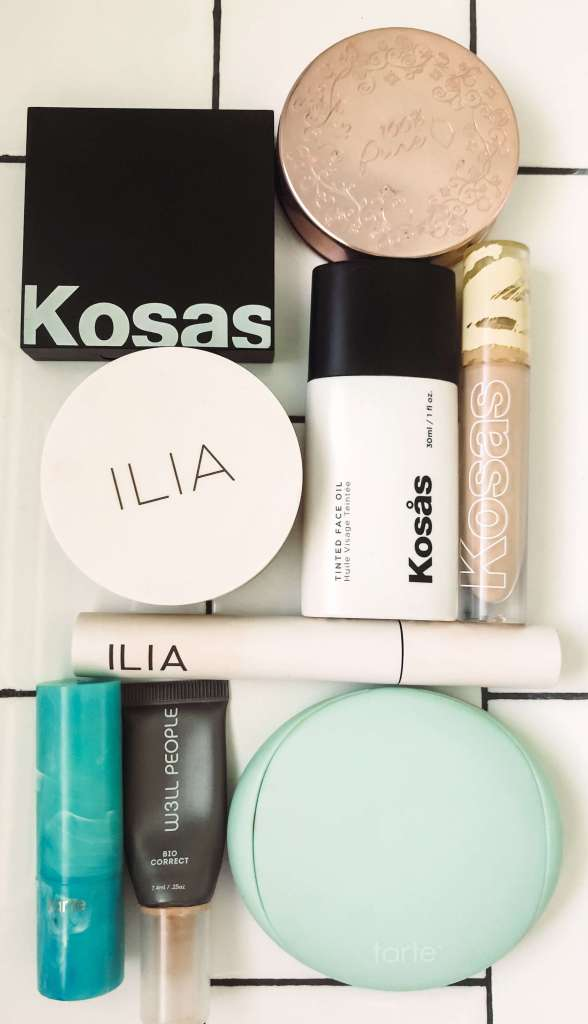 clean beauty brand products laying on white subway tile