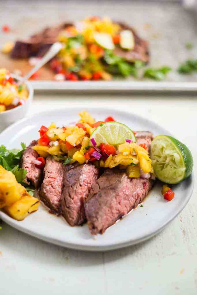 4 strips of grilled flank steak on a white plate topped with pineapple salsa