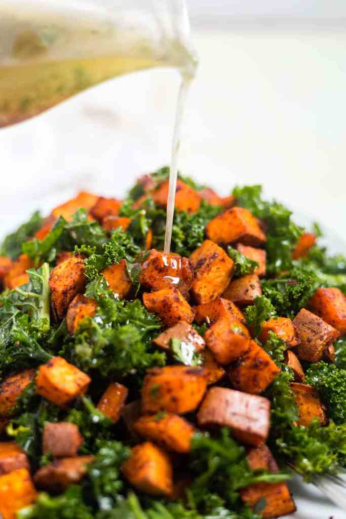 herb vinaigretty being poured over roasted sweet potatoes and massaged kale
