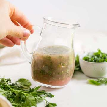 homemade fresh herb vinaigrette in a glass jar with herbs around it