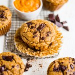 healthy pumpkin muffin unwrapped on a table with chocolate chips
