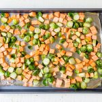 brussels sprouts and sweet potaotes on a sheet pan before roasting