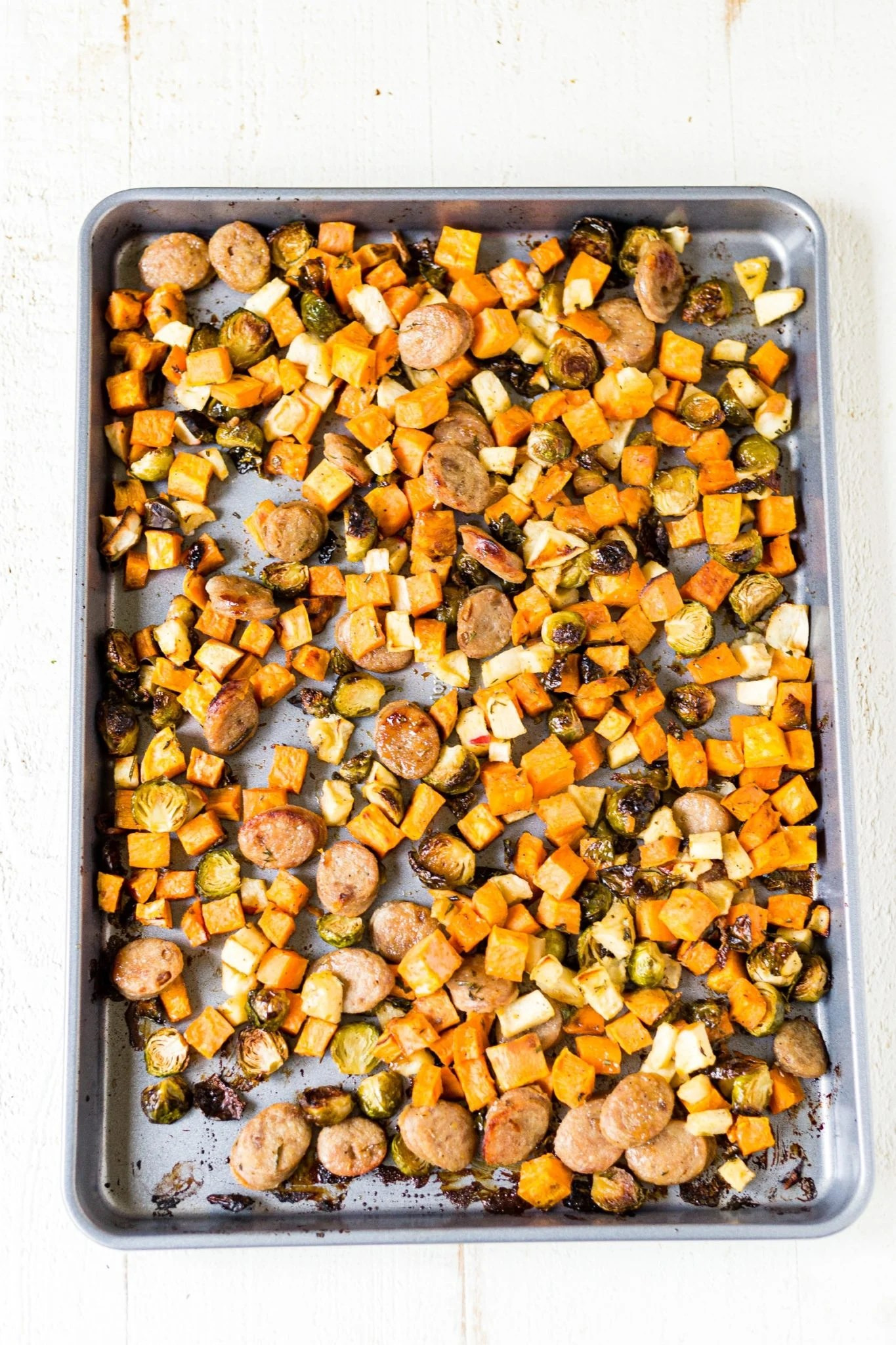 sheet pan filled with roasted sweet potatoes, apples, brussels sprouts and chicken sausage