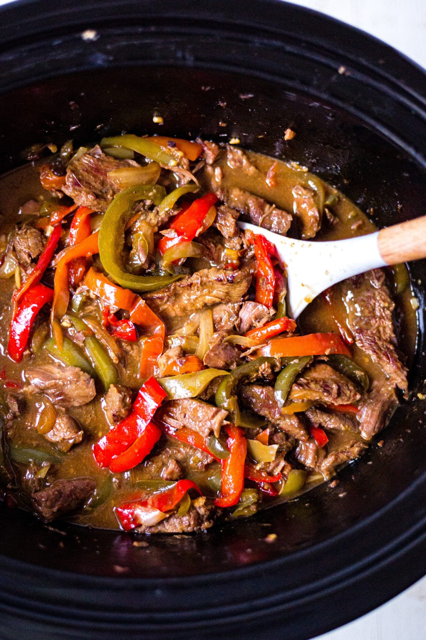 pepper steak reccipe in the crock pot with a serving spoon