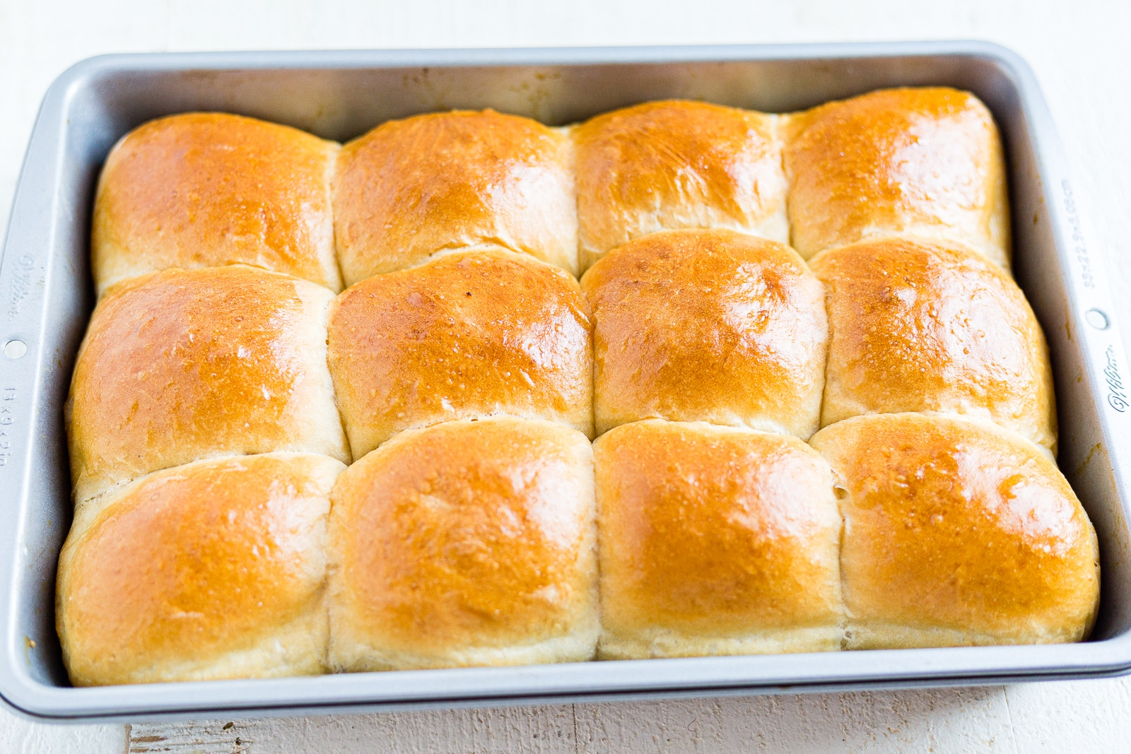 12 baked sourdough rolls in the pan with golden brown tops