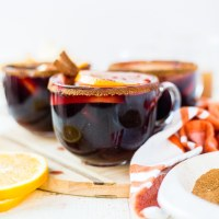 warm winter sangria in a glass mug topped with fresh oranges, apples and cinnamon sticks