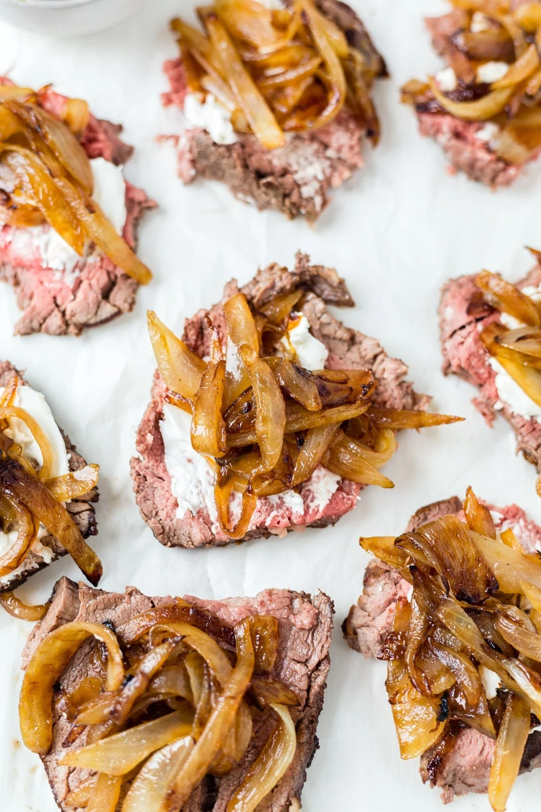 8 pieces of thinly sliced beef tenderloin on a cutting board topped with goat cheese and caramelized onion