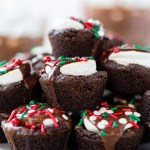 close up of hot cocoa cookies stacked on top of each other with chocolate ganache dripping down the sides