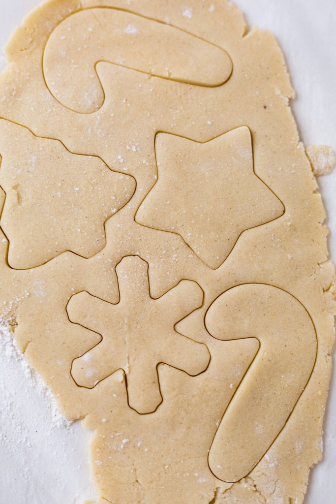 gluten free cut out cookie dough rolled out with christmas shapes cut into it