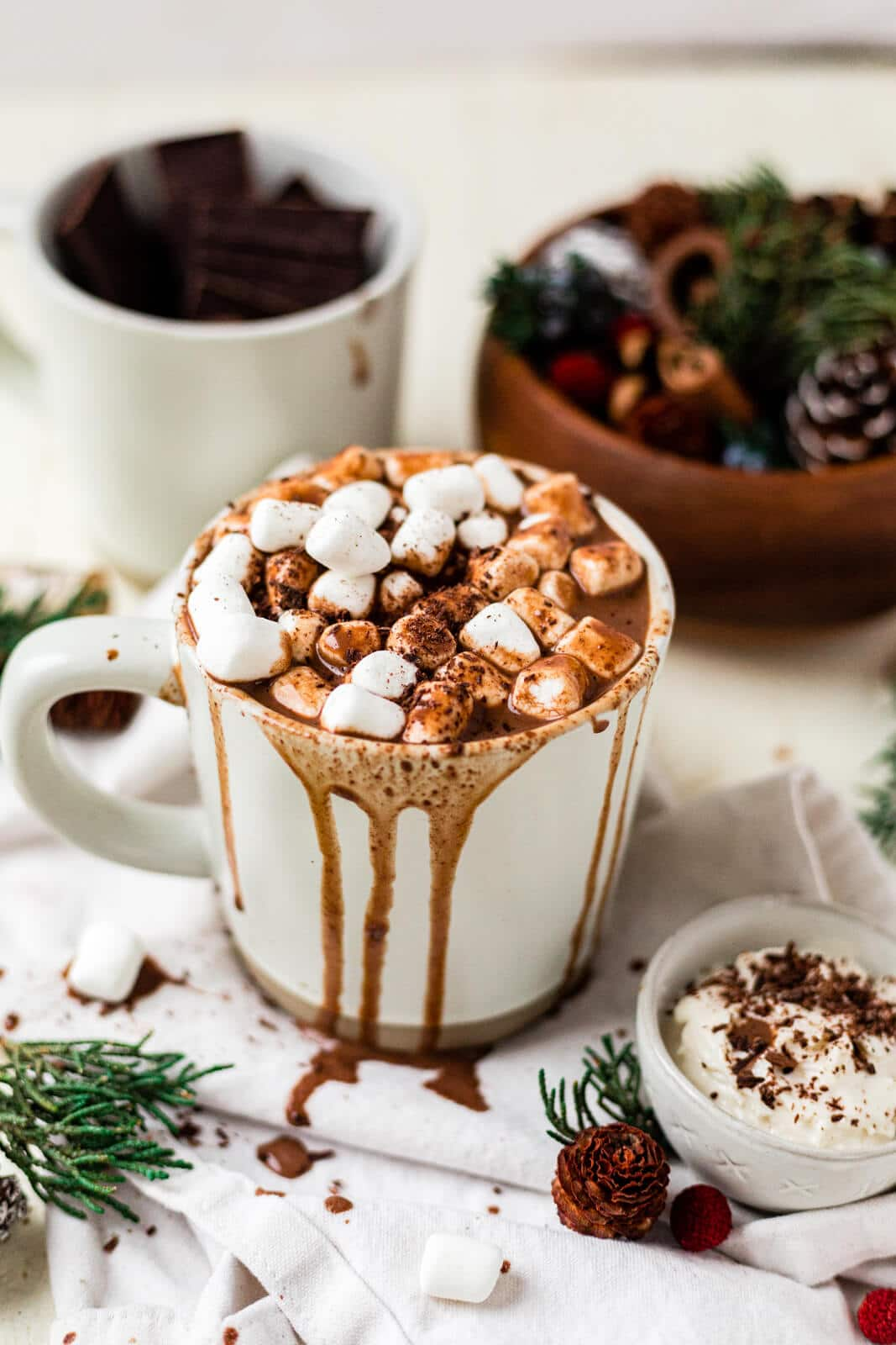 healthy hot chocolate in a white mug with mini marshmallows and hot chocolate dripping over the sides