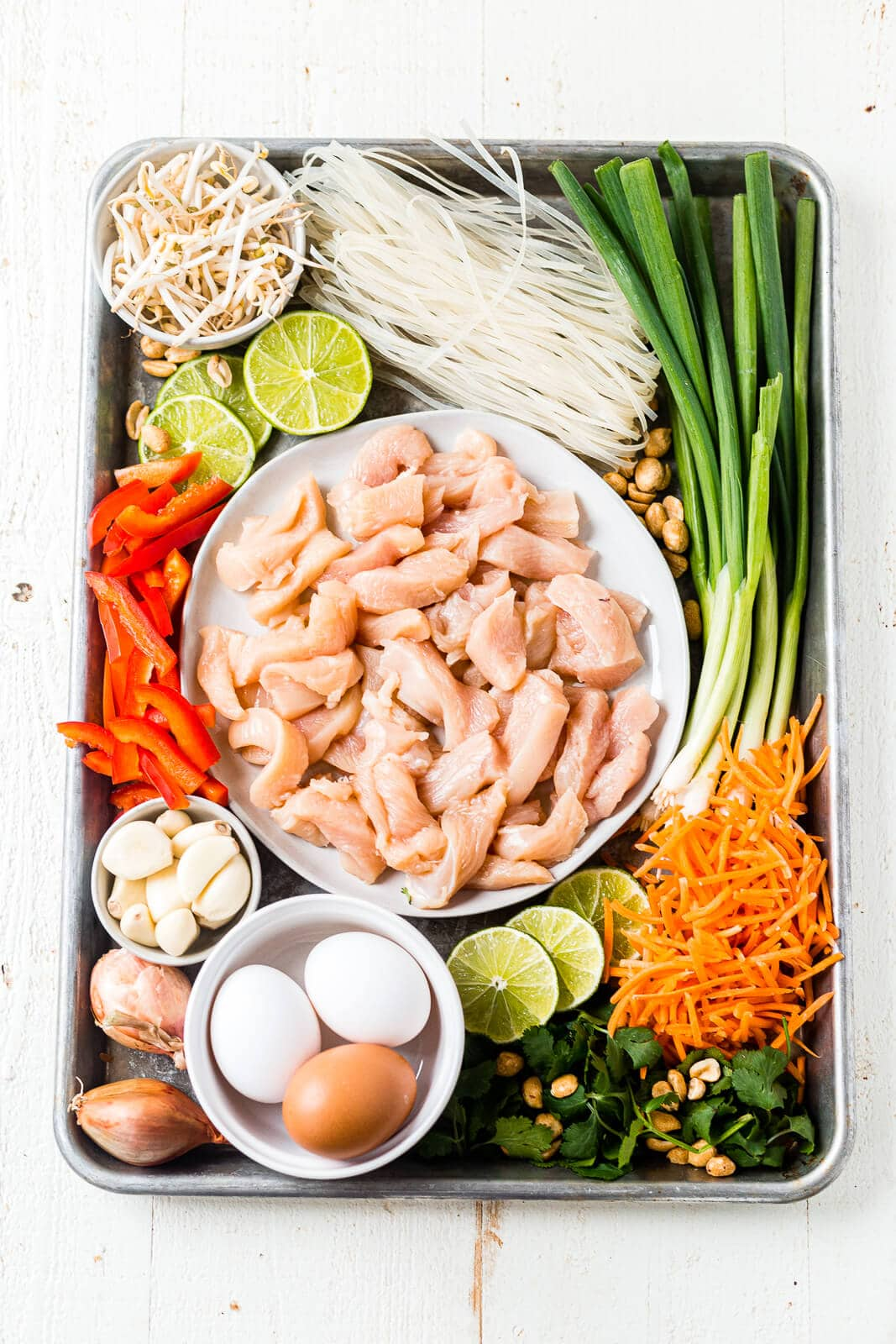 all of the ingredients for chicken pad thai arranged on a sheet pan