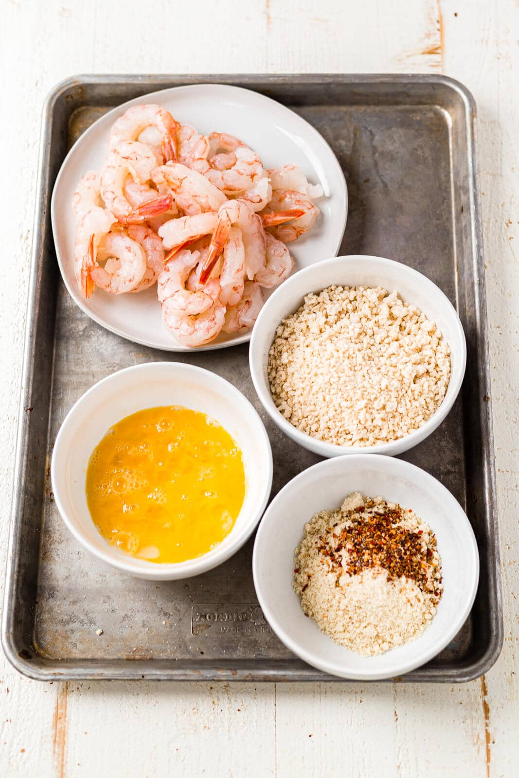 all of the ingredients for crispy air fryer shrimp sitting on a sheet pan before being breaded and cooked