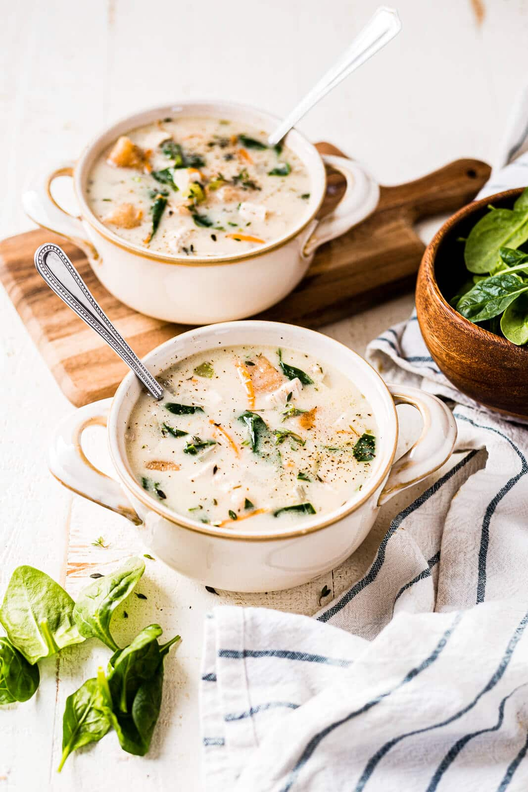 two bowls of copycat olive garden chicken gnocchi soup in bowl with spoons and a blue and white striped napkin next to them
